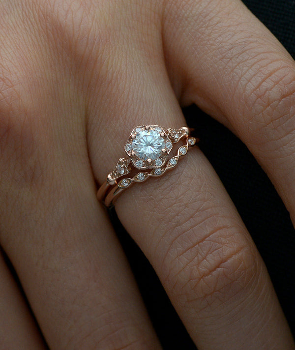 rose gold round halo flower engagement ring with band in a hand