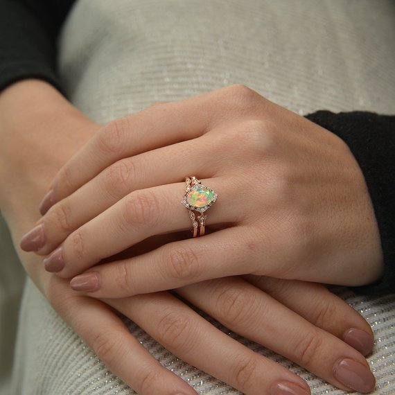 oval opal engagement ring in rose gold in a hand