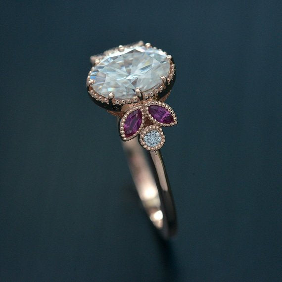 Oval engagement ring with marquise rubies in rose gold side view