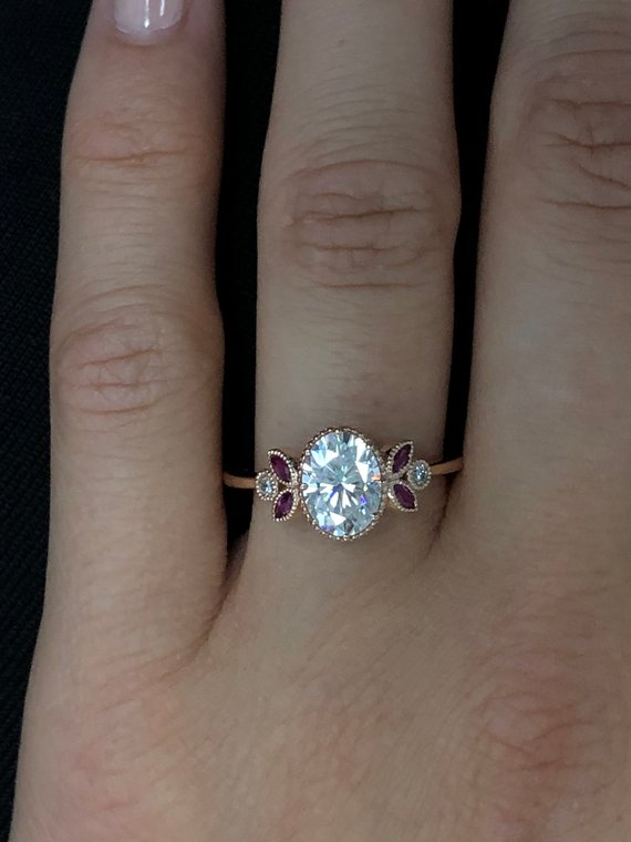 Oval engagement ring with marquise rubies in rose gold in a hand