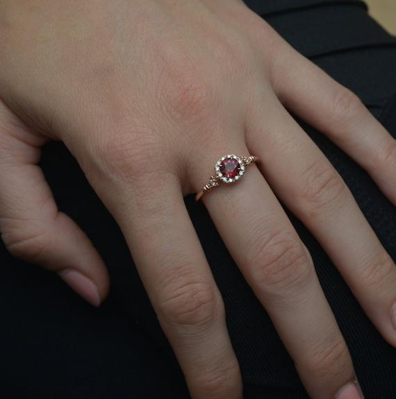 rose gold cushion halo engagement ring red garnet red center in a hand