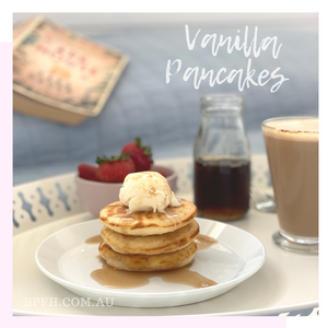 Vanilla pancake stack with vanilla ice cream and maple syrup, on a breakfast tray with coffee and fresh strawberries