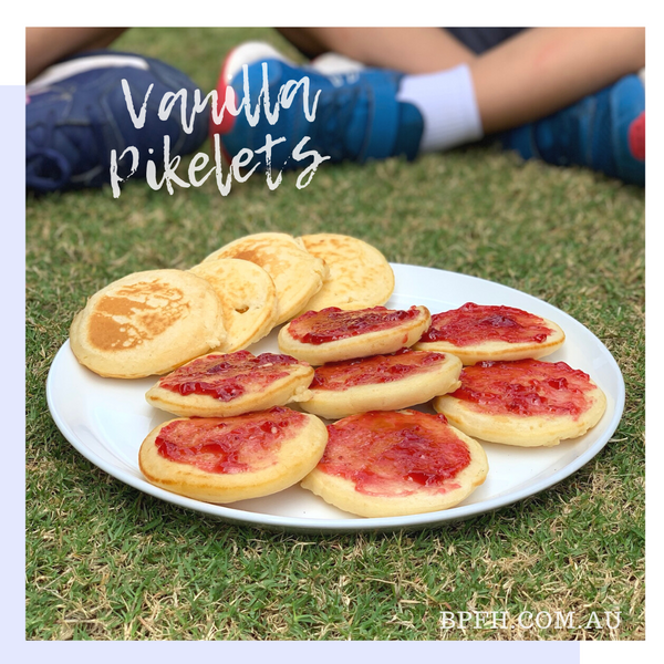 Plate of vanilla pikelets with strawberry jam.