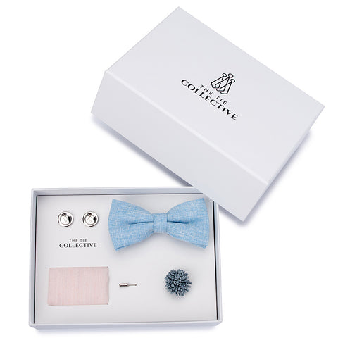 bow tie set featuring a baby blue bow tie with a nude pastel pocket square, a baby blue flower lapel pin and silver button cufflinks.
