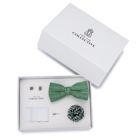 Pastel green cotton bow tie, with a white pocket square, green and grey flower lapel pin, silver rose cufflinks. All packaged together in a white box to highlight individual items.