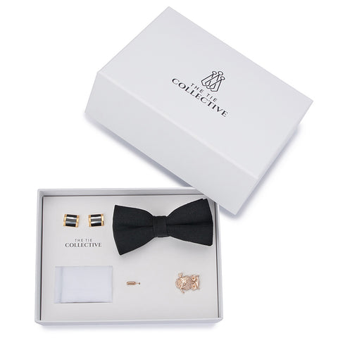 Black bow tie set with a white pocket square, gold owl lapel pin and black and gold cufflinks.