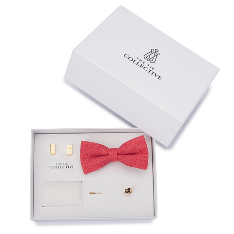 A bow tie set featuring a red, cotton bow tie, a white, cotton pocket square, gold skull lapel pin and gold bullion cufflinks