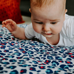 baby on playmat tummy time leopard print