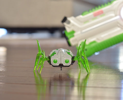 A small green spider-like device from Kidzlane on the center of a wood floor with part of a green laser gun in the background
