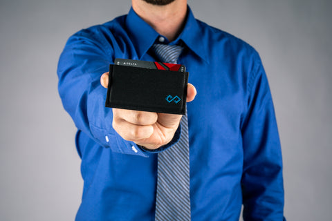 Man in blue dress shirt holding Infinity Wallet outstretched toward camera