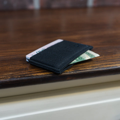 Infinity wallet on table with cash sticking out of the thru pocket