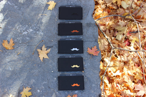 5 Mustache Infinity Wallets laid out on a rock with autumn leaves all around