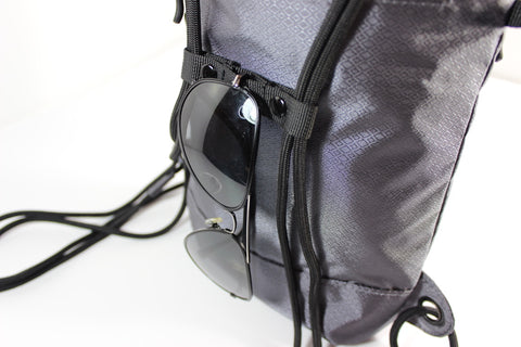 Charcoal Infinity Daypack standing up with Sunglasses hanging from Infinity Sternum Strap