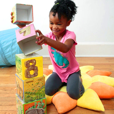 Girl stacking blocks on sun pillow - Floor Bloom