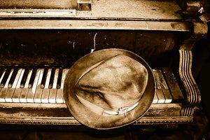 Sepia toned Fedora on an old piano keyboard