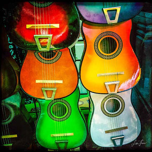 Brightly-colored guitars in varying shades of red, orange, blue-green and white, with reflections.