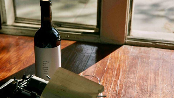 a bottle of Lost Poet red wine on a wooden desk next to a typewriter where Atticus Poetry writes his poems for his next bestselling book
