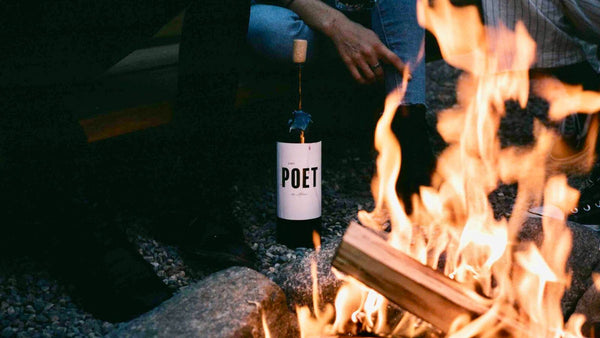 a bottle of Lost Poet wine being enjoyed by friends next to an outdoor campfire