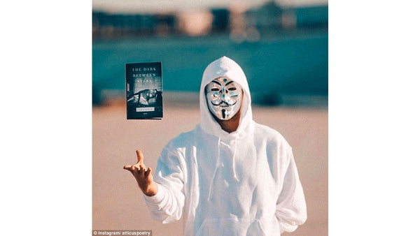 """Atticus poetry wearing his mask and holding a copy of his poetry book """"The Dark Between Stars"""" - Atticus poetry gifts, clothing, and books online are not provided by Rupi Kaur"""