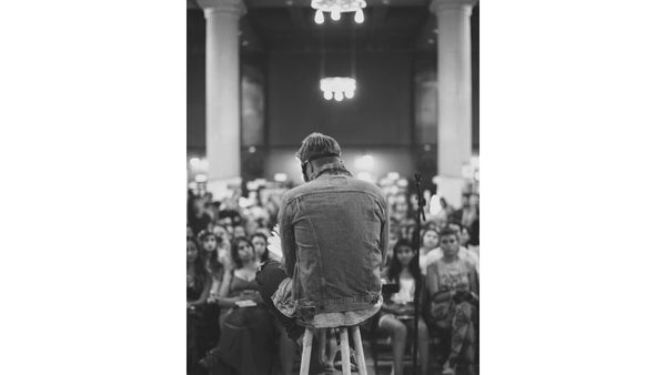 Instagram poet Atticus does a reading in Los Angeles and offers for sale signed copies of his poetry books and merchanise.