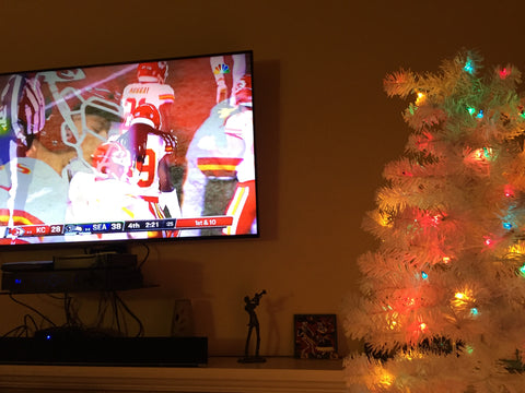 Kansas City Chiefs NLF Game on Big Screen next to White Christmas Tree with lights
