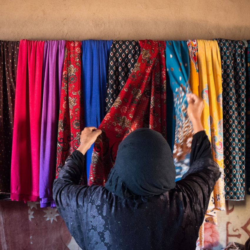 Iraqi Woman selecting fabric from a wall