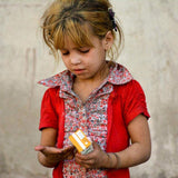 Small girl holding juice box donated by Preemptive Love Coalition