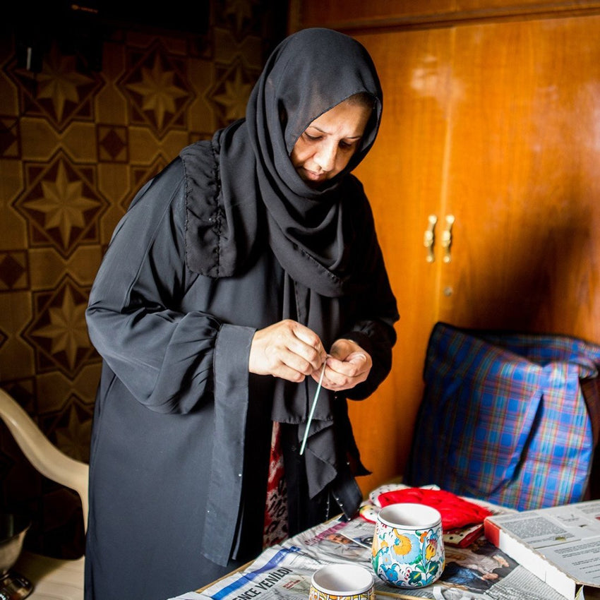 Refugee Woman pouring candles by hand in Iraq
