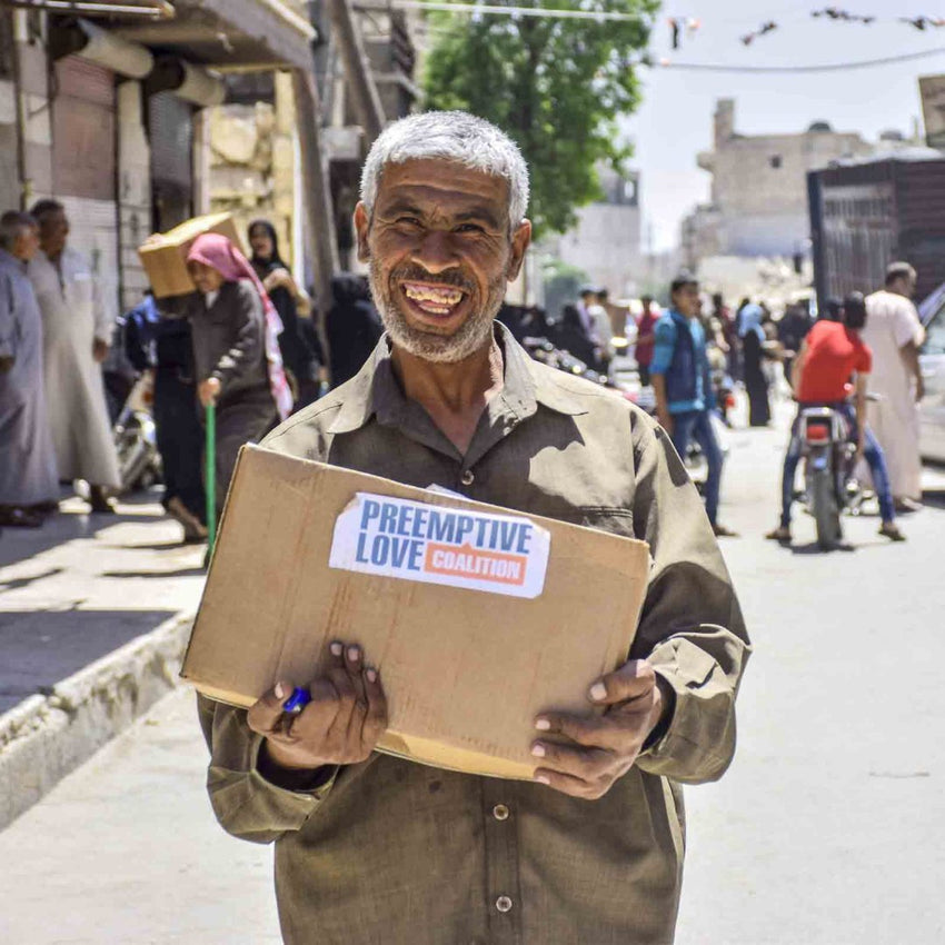 Smiling man holding donated food.