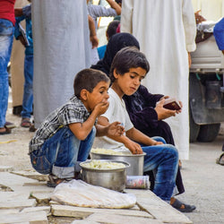 Refugee children eating food donated by you!