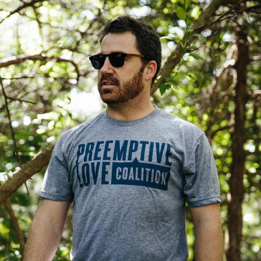 Man wearing Preemptive Love Logo tshirt in a park
