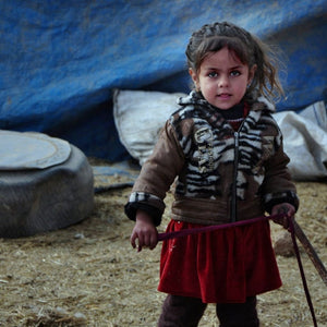Sweet precious refugee girl in front of a temporary tarp shelter in Iraq