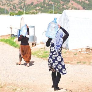 refugees carry water back to their homes