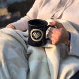 Woman in a cozy blanket holding a beautiful hand thrown stoneware mug