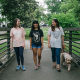 Three women with a dog walking in a park wearing Preemptive Love Spring shirts. Women's fashion and style