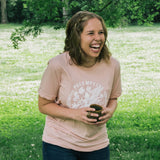 Woman laughing in a park wearing blush shirt for Preemptive Love Coalition