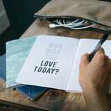 person writing in a journal. Who will you love today?