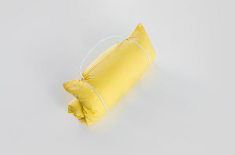 A pure down travel pillow rolled up for convenience