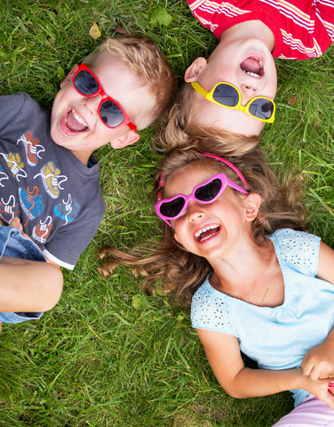 three kids laying in grass laughing