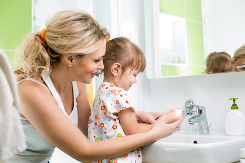 mom helping daughter with washing her hands