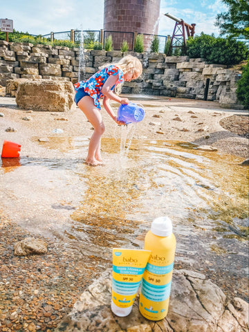 Young girl palying with water at the beach being protected by the right SPF sunscreen
