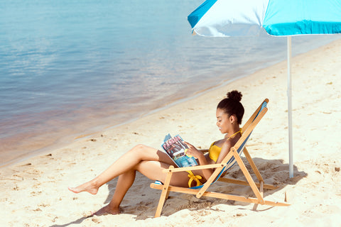 woman sunbathing and reading a magazine at the beach
