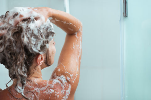 Woman washing her hair with products that contain aloe vera for hair