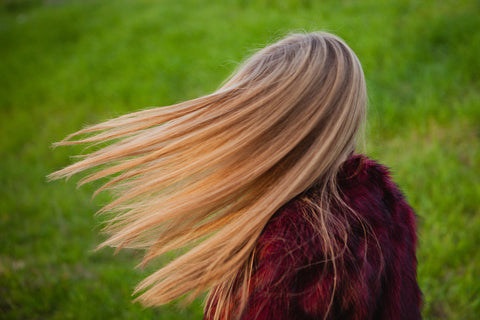 Womans hair flowing in the wind after she uses aloe vera for hair car