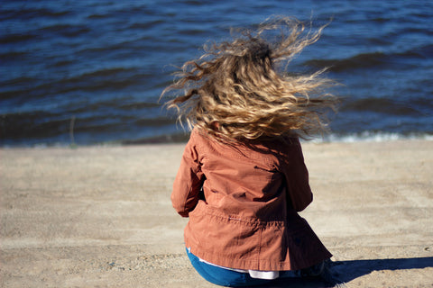 Woman sitting at beach with her hair blowing in the wind