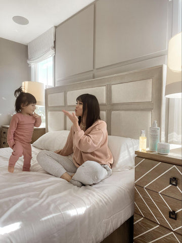 Mom blowing kisses to daughter in bed