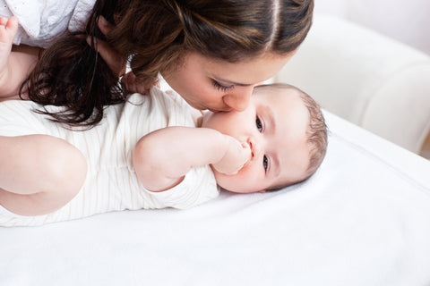 mom kissing newborn cheek
