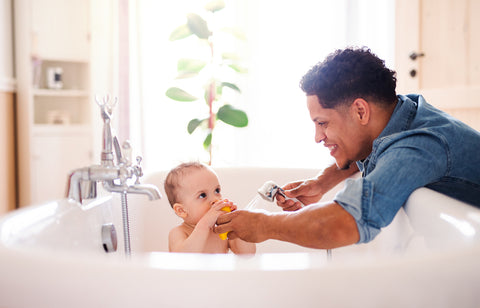 dad giving baby a bath as part of baby bedtime routine