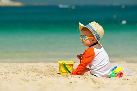 Baby at beach wearing a hat to protect him from the sun