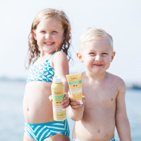 Two kids at the beach holding Babo Botanicals baby sunscreen